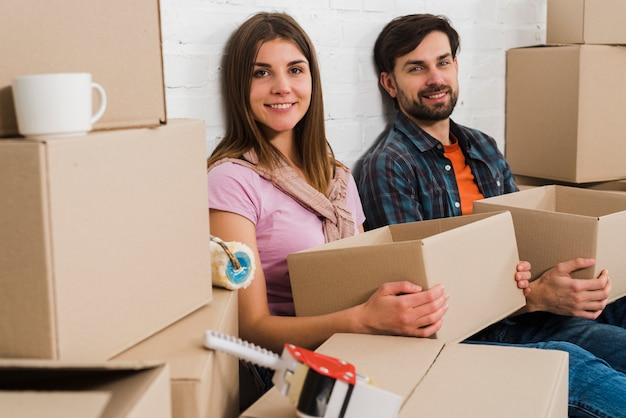 Smiling young couple holding cardboard boxes relaxing in new house Free Photo