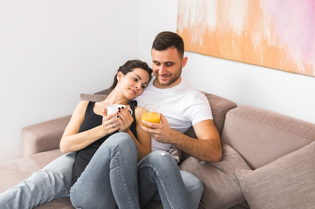 Smiling young couple holding coffee cup and juice glass on sofa Free Photo