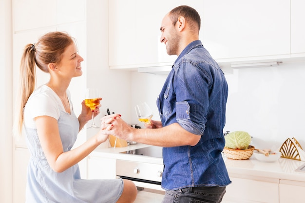 Smiling young couple holding each other's hand holding wineglasses in hand looking at each other Free Photo