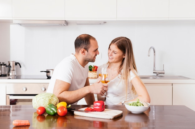 Smiling young couple holding glasses of wine looking at each other Free Photo
