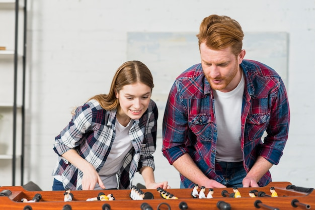 Smiling young couple playing the indoor soccer game at home Free Photo