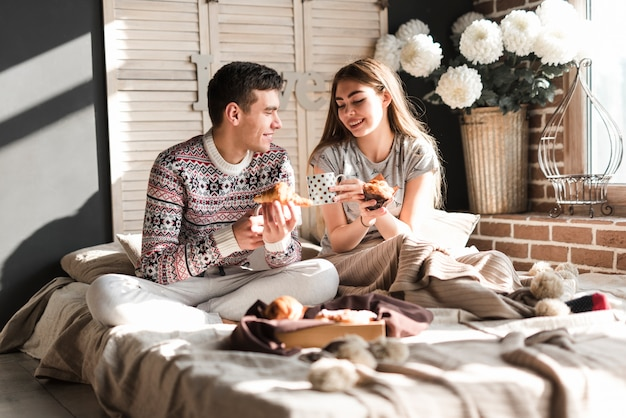 Smiling young couple sitting on bed holding croissant and cupcake in hand Free Photo