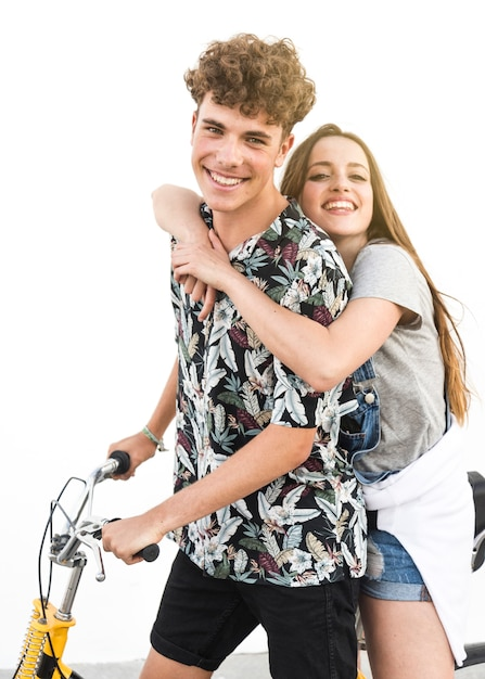 Smiling young couple sitting on bicycle against white background Free Photo