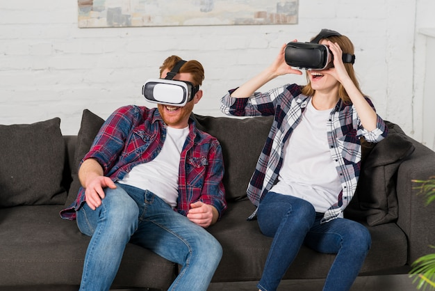 93d00c6c7338 Smiling young couple sitting on black sofa using a vr headset at ...