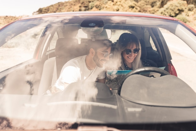 Smiling young couple sitting inside the car looking at map Free Photo