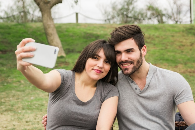 Smiling young couple taking self portrait on cell phone in the park Free Photo
