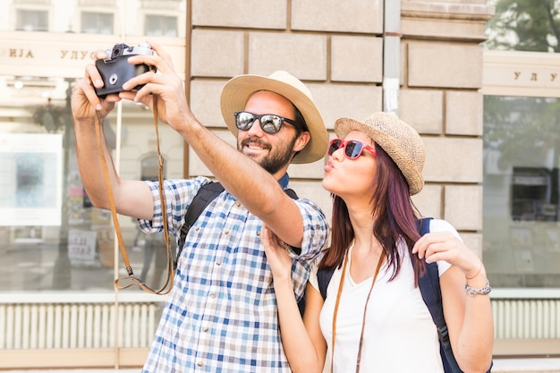 Smiling young couple taking selfie on camera Free Photo
