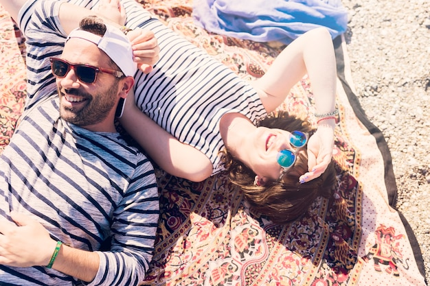 Smiling young couple wearing sunglasses lying on blanket Free Photo