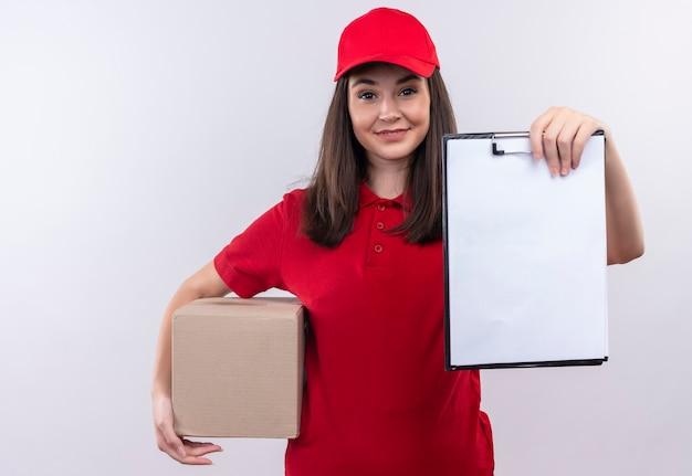 孤立した白い壁にボックスとクリップボードを保持している赤い帽子に赤いtシャツを着て笑顔の若い配達の女性 無料写真