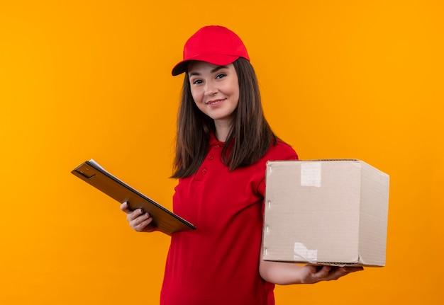 孤立した黄色の壁にボックスとクリップボードを保持している赤い帽子に赤いtシャツを着ている若い配達の女性を笑顔 無料写真