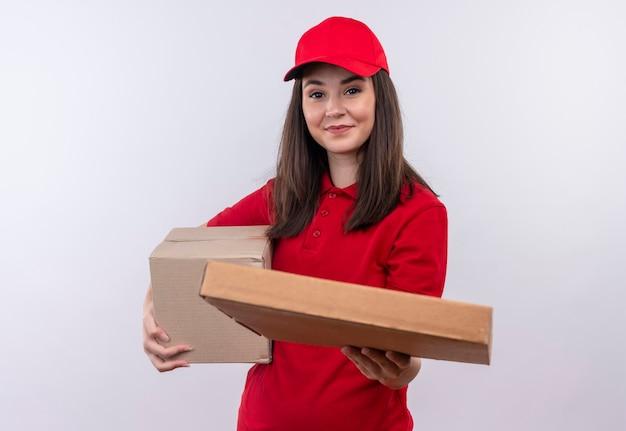 ボックスを保持している赤い帽子に赤いtシャツを着ている若い配達の女性の笑顔と孤立した白い壁にピザの箱を差し出します 無料写真