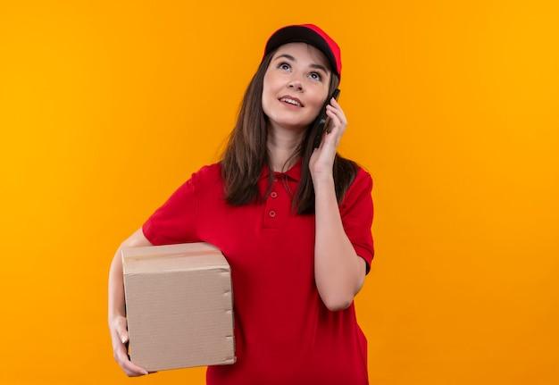 箱を持って、孤立したオレンジ色の壁に電話をかける赤い帽子に赤いtシャツを着ている若い配達の女性を笑顔 無料写真