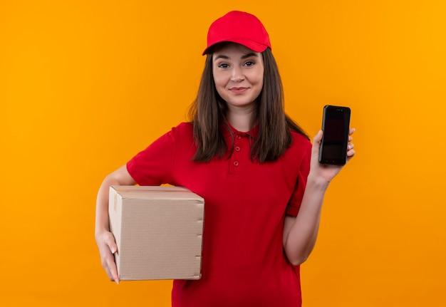 孤立したオレンジ色の壁にボックスと電話を保持している赤い帽子に赤いtシャツを着ている若い配達女性の笑顔 無料写真