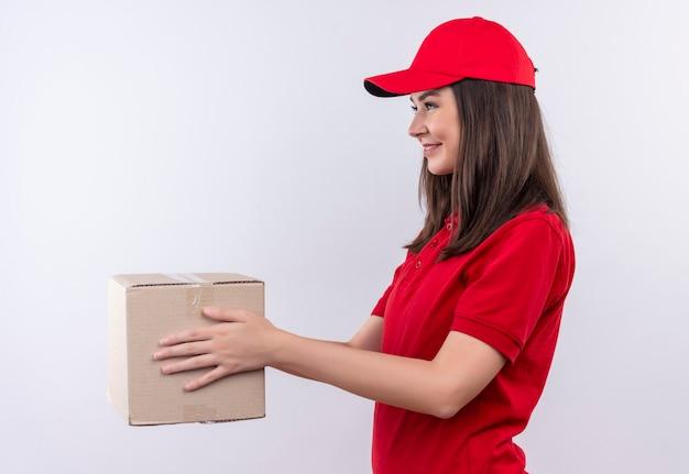 孤立した白い壁にボックスを保持している赤い帽子に赤いtシャツを着ている若い配達の女性を笑顔 無料写真