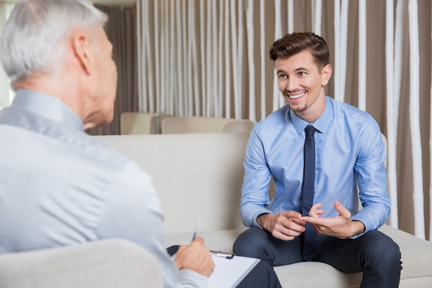 Smiling young employee talking to business leader Free Photo