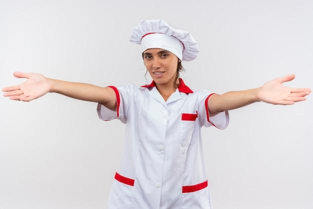 Sorridente giovane femmina cuoco indossando lo chef uniforme tendendo le mani alla telecamera Foto Gratuite