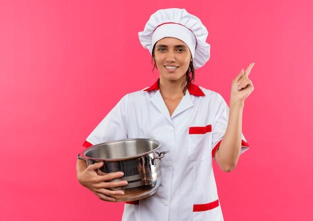 シェフの制服を着た若い女性料理人の笑顔-鍋と蓋を持ってコピースペースを横に向ける 無料写真
