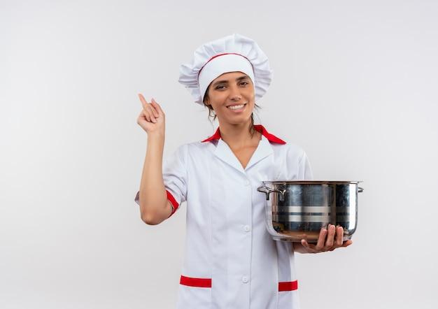 鍋を保持し、コピースペースで横を指すシェフの制服を着て笑顔の若い女性料理人 無料写真