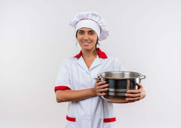コピースペースと鍋を保持しているシェフの制服を着て笑顔の若い女性料理人 無料写真