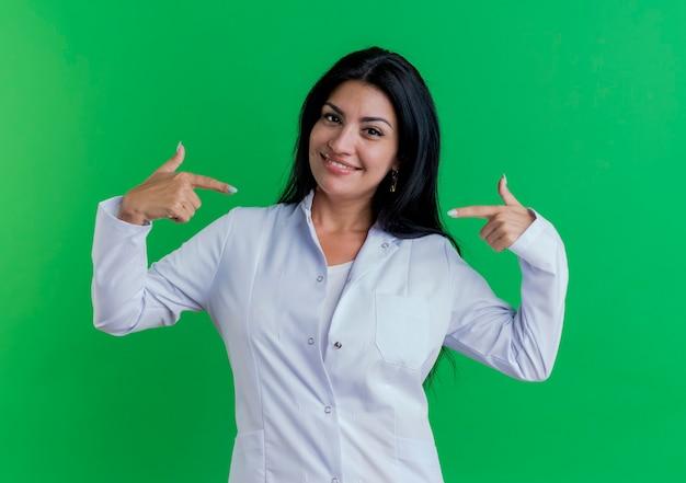 Sorridente giovane donna medico indossa abito medico guardando e indicando se stessa Foto Gratuite