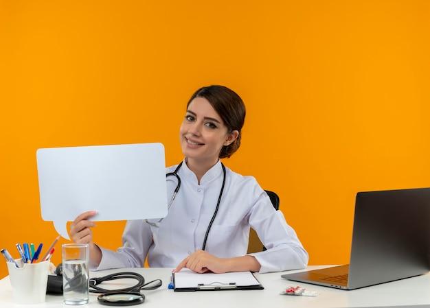 청진 기 격리 노란색 배경에 채팅 거품을 들고 컴퓨터에서 책상 작업에 앉아 의료 가운을 입고 웃는 젊은 여성 의사 무료 사진