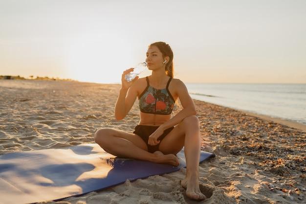 Sorridente giovane femmina di bere acqua fresca e ascoltare musica in cuffia dopo l'allenamento. giovane donna atletica che si esercita vicino al mare. tramonto estivo. Foto Gratuite