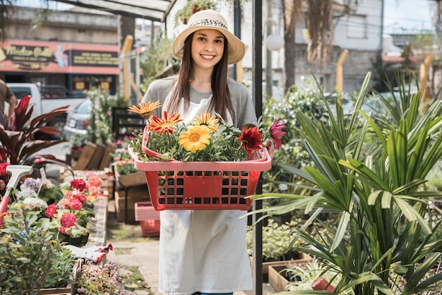 Smiling young female gardener holding colorful flowers in container Free Photo