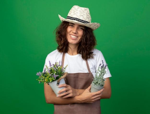 Sorridente giovane giardiniere femminile in uniforme che indossa cappello da giardinaggio tenendo e incrocio di fiori in vasi da fiori isolati sulla parete verde Foto Gratuite