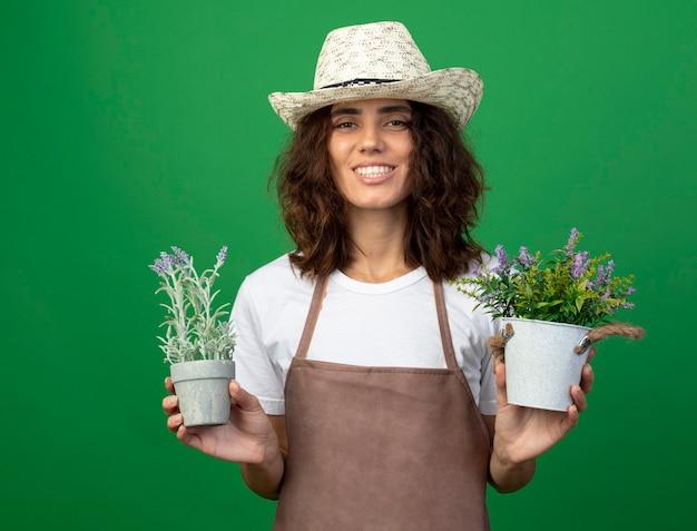 Sorridente giovane giardiniere femminile in uniforme che indossa cappello da giardinaggio tenendo i fiori in vasi da fiori isolati sulla parete verde Foto Gratuite