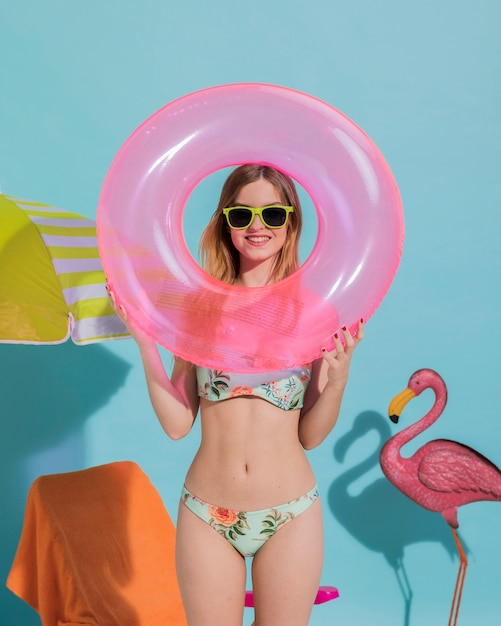 Smiling young female holding swimming ring in studio Free Photo