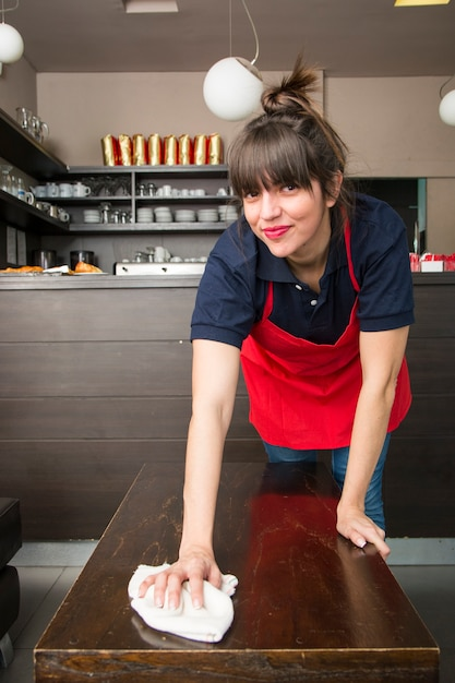 Smiling young female waitress cleaning the table with napkin Free Photo