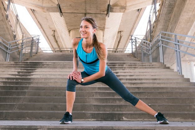 Smiling young fitness female runner stretching her legs before running on staircase Free Photo