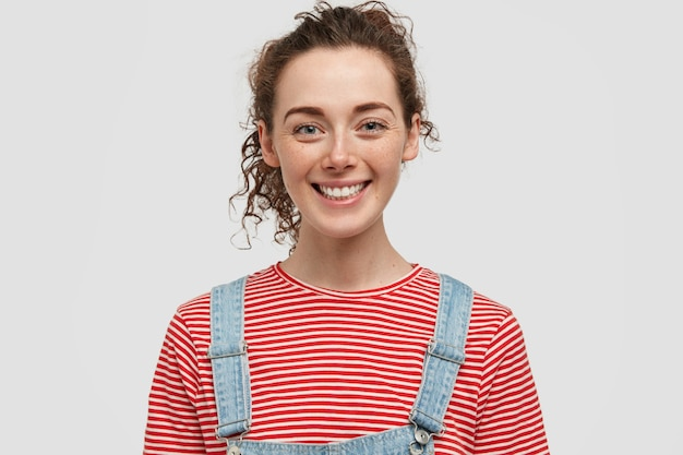 ポジティブな表情で笑顔の若いそばかすのあるヨーロッパの女性は、陽気な表情をしており、デニムのオーバーオールと赤い縞模様のセーターを着て、気分が良く、白い壁に隔離されています 無料写真