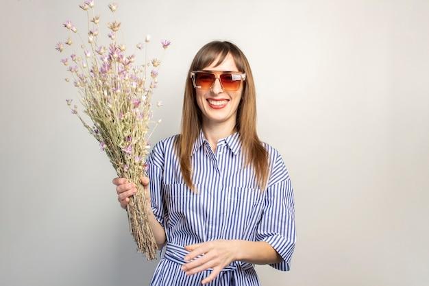 Улыбающаяся молодая девушка в солнцезащитных очках держит букет полевых цветов на светлом фоне Premium Фотографии