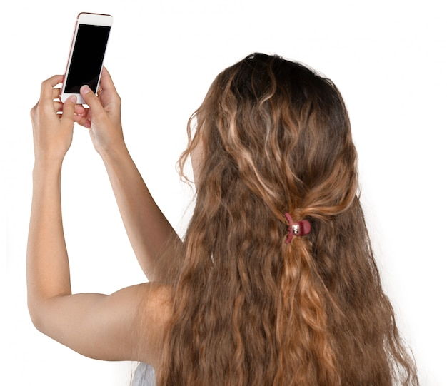 Smiling young girl making selfie photo on smartphone Premium Photo