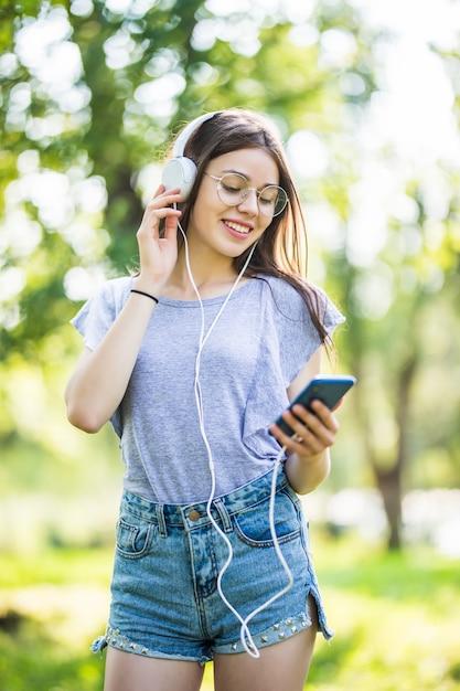 Sorridente studentessa giovane con zaino tenendo il telefono cellulare, passeggiate al parco, ascoltando musica con gli auricolari Foto Gratuite