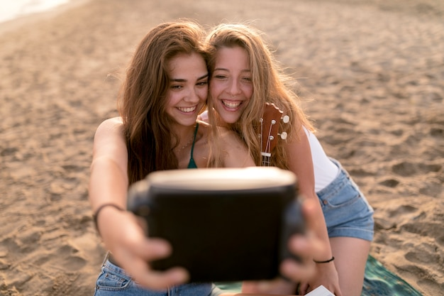 Smiling young girls taking self portrait from instant camera at beach Free Photo