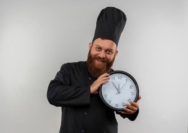 Sorridente giovane cuoco bello in uniforme del cuoco unico che tiene orologio che sembra isolato su spazio bianco Foto Gratuite