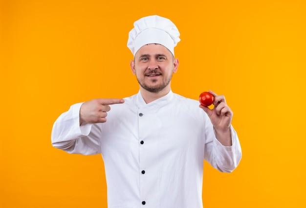 オレンジ色のスペースで隔離のトマトを保持し、指してシェフの制服を着た若いハンサムな料理人の笑顔 無料写真
