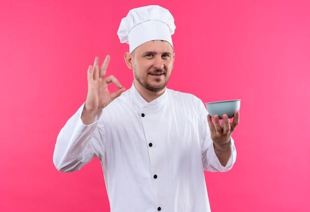 ピンクのスペースで隔離のokサインをやってボウルを保持しているシェフの制服を着た若いハンサムな料理人の笑顔 無料写真