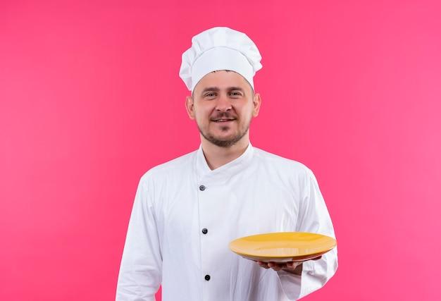 ピンクのスペースで隔離空のプレートを保持しているシェフの制服で若いハンサムな料理人の笑顔 無料写真