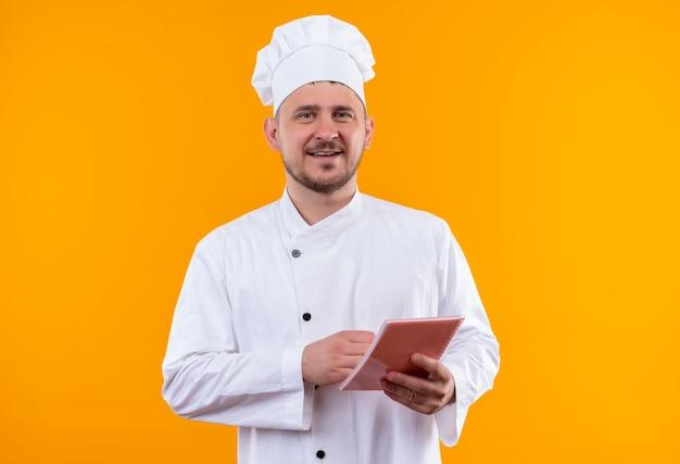オレンジ色のスペースで隔離のメモ帳を保持しているシェフの制服で若いハンサムな料理人の笑顔 無料写真