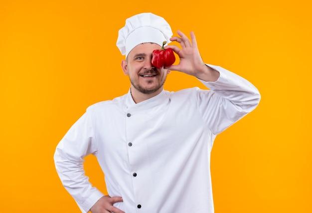 オレンジ色のスペースで隔離の目にコショウを置くシェフの制服を着た若いハンサムな料理人の笑顔 無料写真