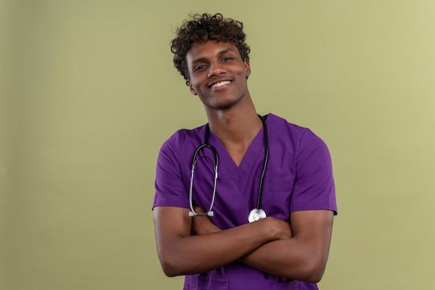 Un sorridente giovane bello di carnagione scura medico con i capelli ricci che indossa uniforme viola con uno stetoscopio tenendo le mani giunte mentre su uno spazio verde Foto Gratuite