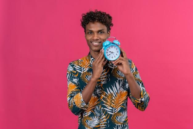 Улыбающийся молодой красивый темнокожий мужчина с вьющимися волосами в рубашке с принтом листьев держит синий будильник и показывает время на розовом фоне Бесплатные Фотографии