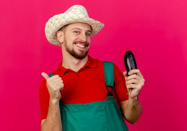 Sorridente giovane giardiniere slavo bello in uniforme e cappello in possesso di melanzane cercando di mostrare il pollice in su Foto Gratuite