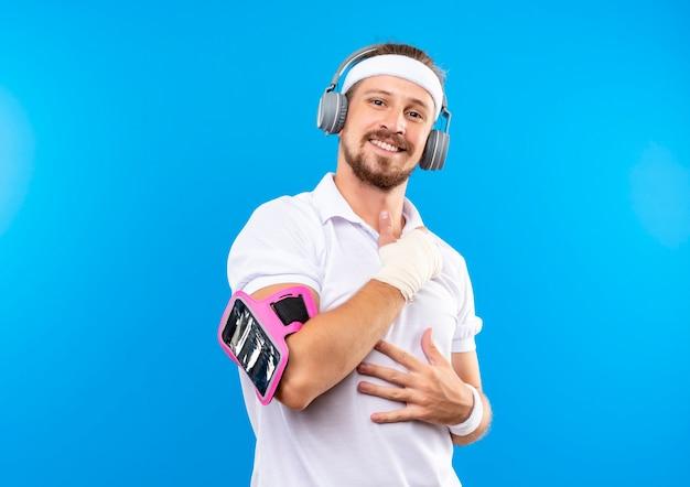 Sorridente giovane uomo sportivo bello che indossa fascia e braccialetti e cuffie con fascia da braccio del telefono che mette le mani sulla pancia e sul petto con polso ferito avvolto con benda isolato su spazio blu Foto Gratuite