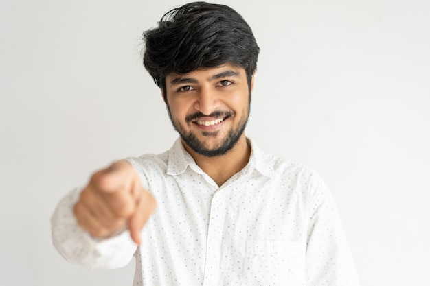 Smiling young indian man pointing at you and looking at camera Free Photo
