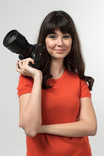 白の長い髪の良い気分でデザインされたtシャツでphotocameraを保持している若い女性を笑顔 無料写真