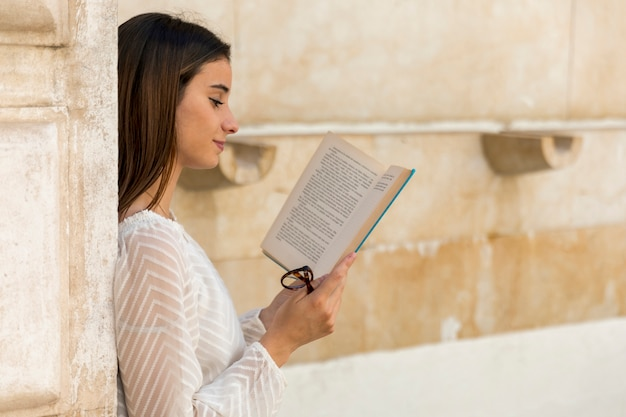 Smiling young lady reading book and holding glasses Free Photo